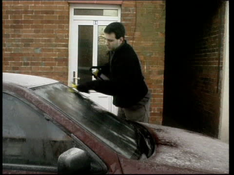 berkshire newbury motorist scraping ice from car windscreen car towards along icy street order ref bsp201299028 - newbury england stock videos & royalty-free footage
