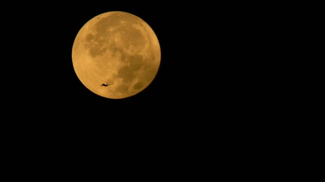 big golden full moon and aircraft - moon stock videos & royalty-free footage