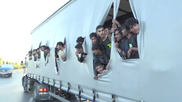 big group of irregular migrants hiding in the back of a truck tore the vehicle's tarpaulin cover to breath fresh air due to hot weather in samsun,... - hiding stock videos & royalty-free footage