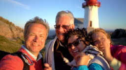 A big happy family takes a selfie or Uses Phone Video Call Camera on the seacoast with an old lighthouse