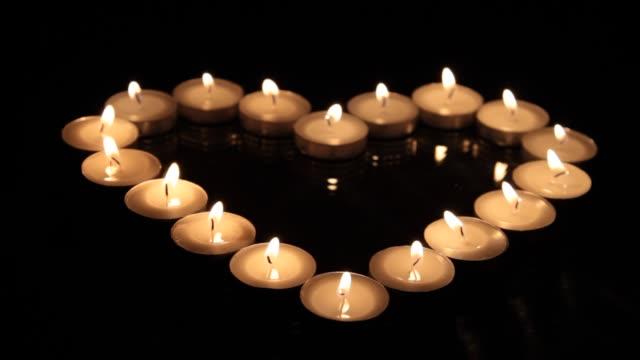 vidéos et rushes de grand coeur des petites bougies allumées - candlelight
