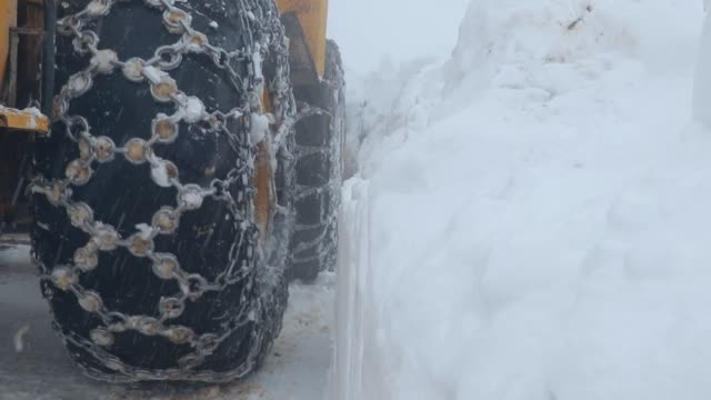 a big machine clears snow from the road - construction equipment stock videos & royalty-free footage