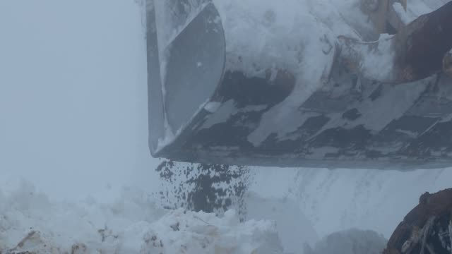 a big machine clears snow from the road - bulldozer stock videos and b-roll footage