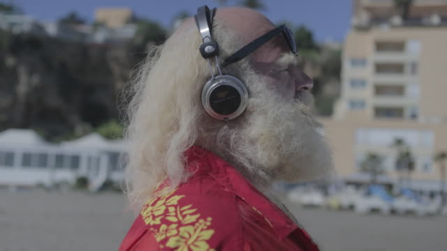 stockvideo's en b-roll-footage met m/s big man w/ white long hair (santa claus), beard and moustache, and hawaiian shirt in the beachlistening to music w/ headphones - electrical equipment