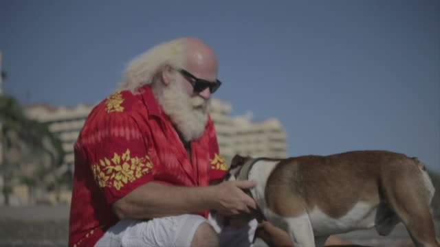 F/S big man w/ white long hair (Santa Claus), beard and moustache, caressing his bulldog in the beach