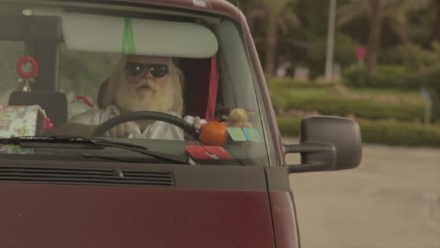 M/S big man w/ white long hair (Santa Claus), beard and moustache driving a van w/ christmas decoration and singing
