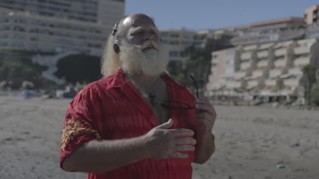 m/s big man w/ white long hair (santa claus), beard and moustache, hawaiian shirt, headphones, in the beach - big hair stock videos & royalty-free footage