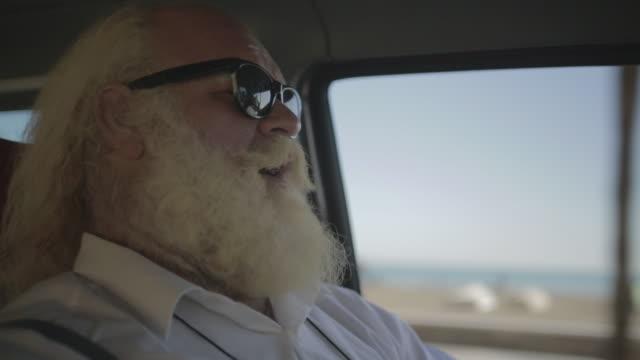 M/S big man w/ white long hair (Santa Claus), beard and moustache, hawaiian shirt, sat in the beach, drinking in a cup