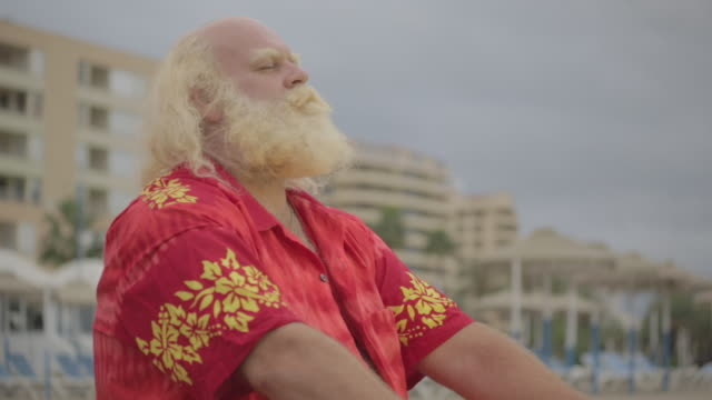 F/S big man w/ white long hair (Santa Claus), beard and moustache sleeping and hangover in the beach