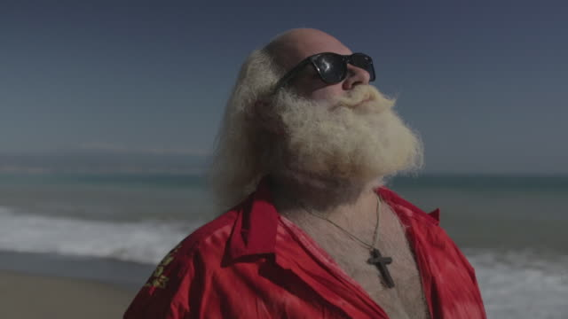 M/S big man w/ white long hair (Santa Claus), beard and moustache, sunglasses and hawaiian shirt in the beach