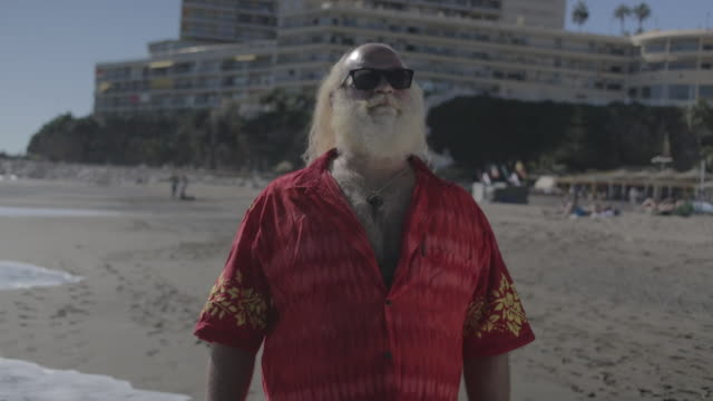 stockvideo's en b-roll-footage met m/s  big man w/ white long hair (santa claus), beard, moustache, sunglasses and hawaiian shirt in the beach - overhemd