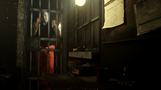 big men standing at door in prison cell with his hands through bars - claustrophobia stock videos & royalty-free footage