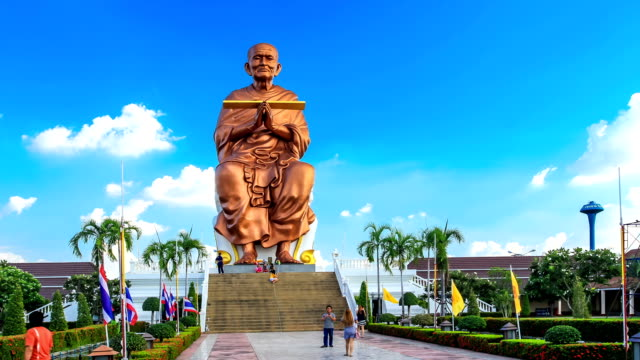 big munk statue against blue sky with people, timelapse - surat thani province stock videos & royalty-free footage