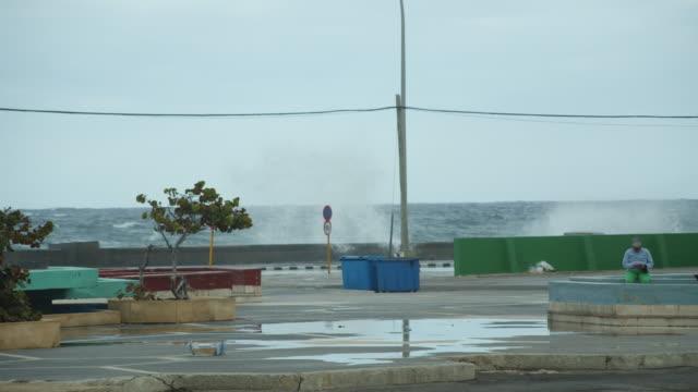 vídeos y material grabado en eventos de stock de big sea waves on the malecon coastal road in havana, cuba on a cloudy day - pared de cemento