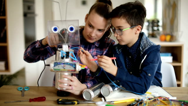 big sister and little brother constructing a robot together - school science project stock videos & royalty-free footage