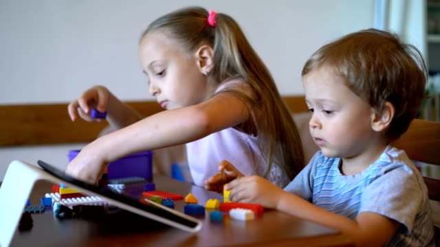 big sister and little brother playing with plastic bricks at home - brother stock videos & royalty-free footage