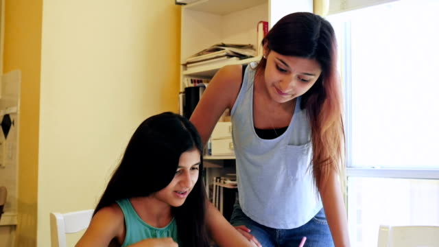 big sister helping preteen girl with her math homework in family kitchen - bending over stock videos & royalty-free footage