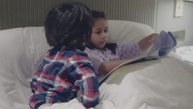 big sister reading fairytale to little boy in their apartment - offspring stock videos & royalty-free footage
