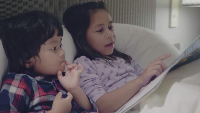 vídeos de stock e filmes b-roll de big sister reading fairytale to little boy in their apartment - irmãos