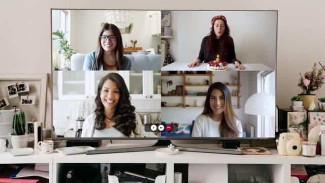 vidéos et rushes de grand moniteur de télévision avec un appel de vidéoconférence sur l'écran - amis célébrant une fête d'anniversaire virtuelle - quatre personnes