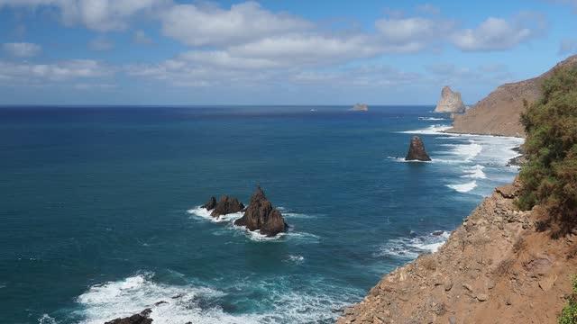 big waves crashing into the tenerife island coast with nice  mountain landscape. - atlantikinseln stock-videos und b-roll-filmmaterial