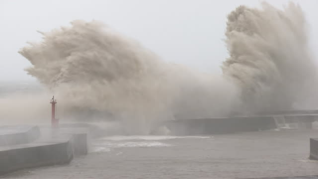 big waves rushing over breakwater, kochi, japan - gezeiten stock-videos und b-roll-filmmaterial