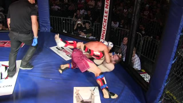 vídeos y material grabado en eventos de stock de / bigger fighter in red trunks takes down smaller fighter in black trunks but while on ground smaller fighter bends other guy's arm in painful... - oficial deportivo