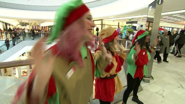 bigger than expected rise in inflation; england: london: int various shots women dressed as christmas elves and dancing tilt down shopping centre... - エルフ点の映像素材/bロール