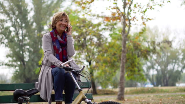vídeos de stock e filmes b-roll de bike commuter senior woman relaxing on the bench in the city - banco assento
