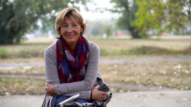 vidéos et rushes de vélo banlieue haute femme reposante sur le banc dans la ville - 60 64 ans