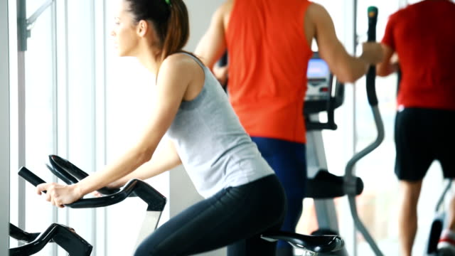 bike exercising in a gym. - brightly lit stock videos and b-roll footage