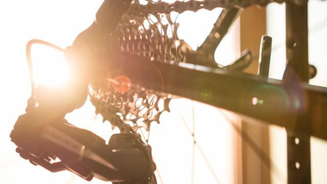 Détail de cadre de vélo, rayons de roue, gear et chaîne au coucher du soleil