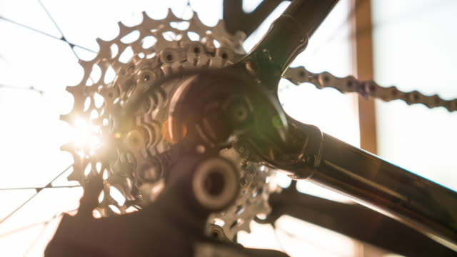 bike frame detail, wheel spoke, gear and chain at sunset - bicycle frame stock videos & royalty-free footage