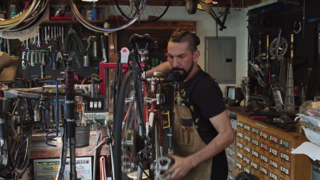 bike mechanic adjusting bicycle on stand and shifting through gears - independence stock videos & royalty-free footage