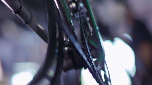 Bike mechanic cranks pedal by hand, inspects bicycle chain, and squeezes brake lever