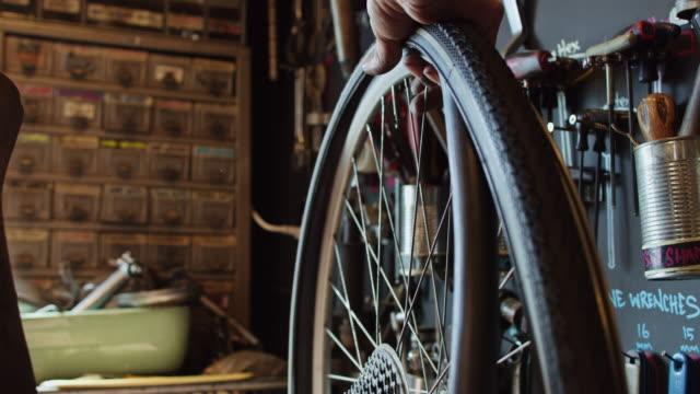 ホイールから内側のチューブを取り外す自転車メカニック - 水泳用浮き輪点の映像素材/bロール