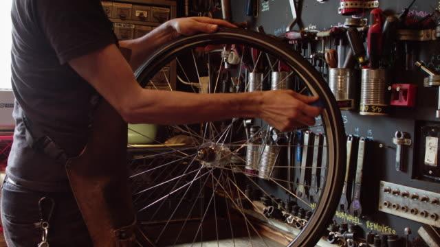 タイヤを取り外すバイクメカニック - 水泳用浮き輪点の映像素材/bロール