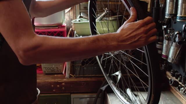タイヤを緩めるためにレバーを使用して自転車メカニック - 水泳用浮き輪点の映像素材/bロール