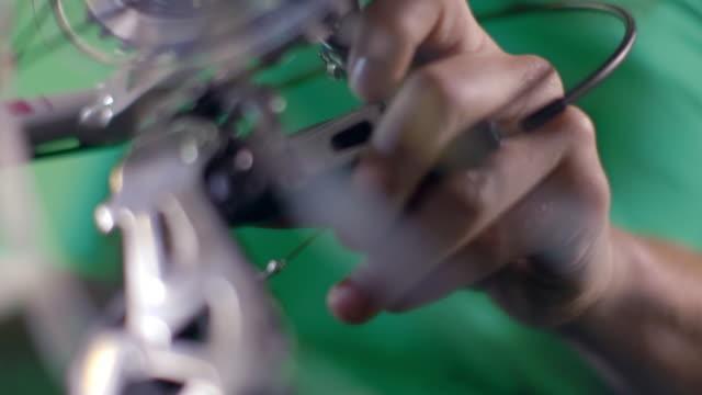 bike mechanic works on rear derailleur pulley as bicycle wheel spins in repair shop - adjusting stock videos & royalty-free footage