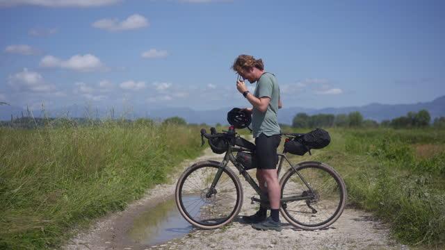 bike packer si ferma per controllare il telefono mentre si perde in campo in bicicletta - etnia video stock e b–roll