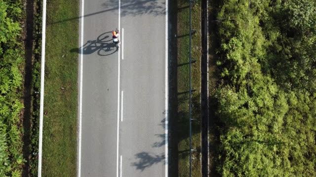 vídeos de stock e filmes b-roll de bike ride road trip at rural area ulu langat with 2 sportswoman athlete rider in the morning drone view - bicicleta de corrida