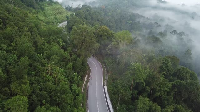 vídeos de stock e filmes b-roll de bike ride road trip at rural area ulu langat with 2 sportswoman athlete rider in the morning drone view - encosta