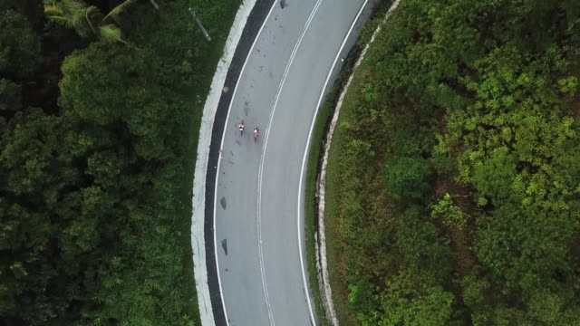 bike ride road trip at rural area ulu langat with 2 sportswoman athlete rider in the morning drone view - following stock videos & royalty-free footage