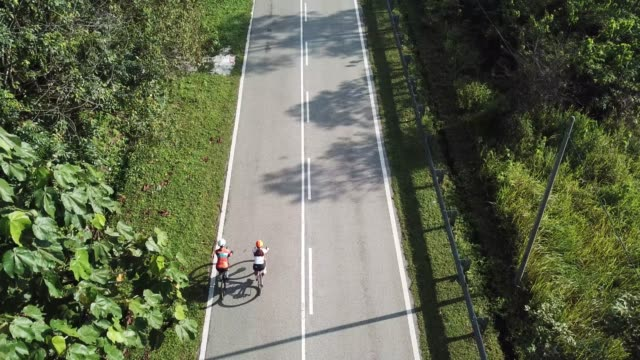 bike ride road trip at rural area ulu langat with 2 sportswoman athlete rider in the morning drone view - malaysia stock videos & royalty-free footage
