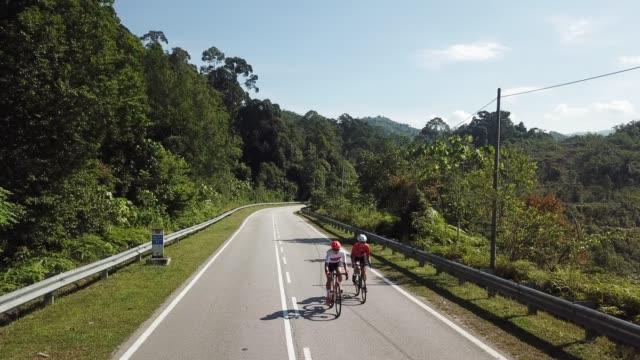 朝のドローンビューで2スポーツウーマンアスリートライダーと農村地域ウルランゴールで自転車に乗るロードトリップ - 女性選手点の映像素材/bロール