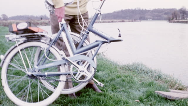1974 montage bike rider cycling to a boat dock, folding and carrying the bike onto a boat, while a chauffeur is taking a bicycle out of car trunk, and unfolding it, as the passenger boards and is riding it away / united kingdom - 1974 bildbanksvideor och videomaterial från bakom kulisserna