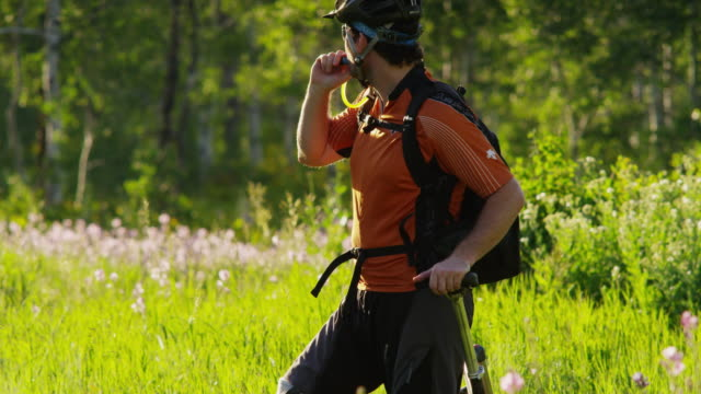 ms tu bike rider with artificial limb taking break and drinking water from backpack on meadow, then riding off / american fork canyon, utah, usa - american fork canyon点の映像素材/bロール
