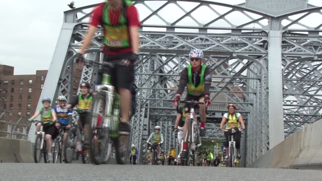 vídeos y material grabado en eventos de stock de bike riders in cycling tour of nyc on bridges over the east river two shots leads to fdr drive - salmini