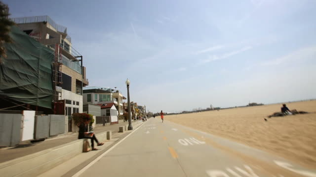 stockvideo's en b-roll-footage met ws pov bike riding along the santa monica boardwalk and passing cyclists, pedestrians and runner / venice, california, usa - westers schrift