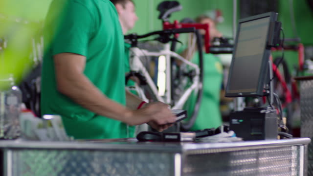 bike shop cashier scans product barcode for customer at sales counter - point of sale stock videos and b-roll footage